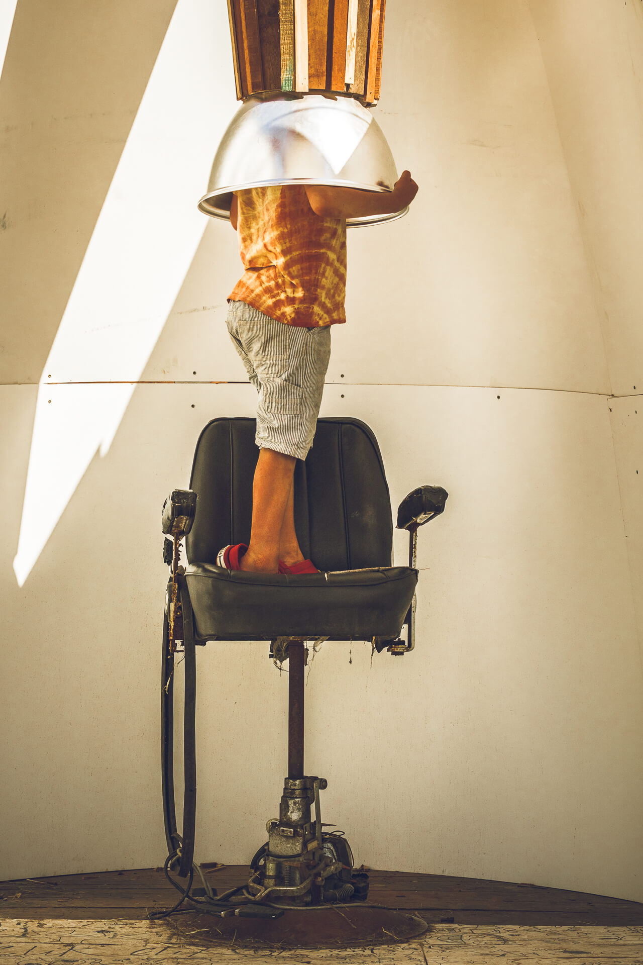 A strange image. In the image can be seen a black coloured adjustable height chair, above which is a hollow bronze coloured tube, with a silver opening that is wide enough for the young boy who is standing on the chair to get his head and shoulders into.