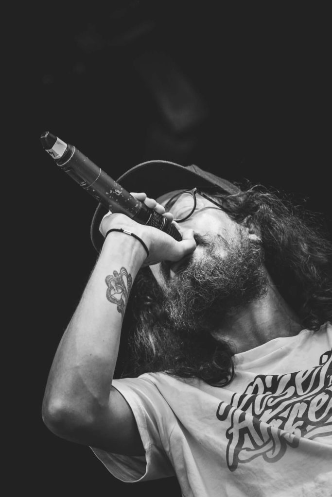In this black & white image (taken at 45 degrees and against a pure black background) seen on the Garden Stage Nozstock in 2018, in a chest up image, a bearded performer from one of the many 'Indy' bands who performed on there. He wears a T-shirt and a baseball cap, and he holds the mic to his mouth.