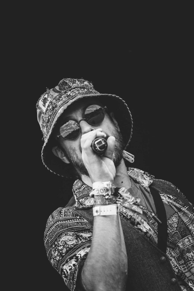 Seen on stage at Nozstock on the Garden Stage in 2018, in a chest up image, a bearded performer from one of the many 'Indy' bands who performed on there. In this black & white image (taken at 45 degrees and against a pure black background) he wears a multi design shirt and a matching beanie hat, along with round black sunglasses, and he holds the mic to his mouth.