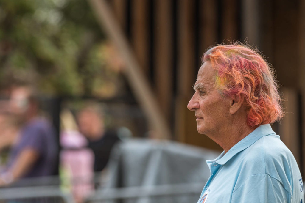 A very simple head & shoulders image of a middle aged gentleman taken at Nozstock in 2018. He stands, all alone, with a vacant gaze. His hair is coloured Red, Yellow, and Orange.