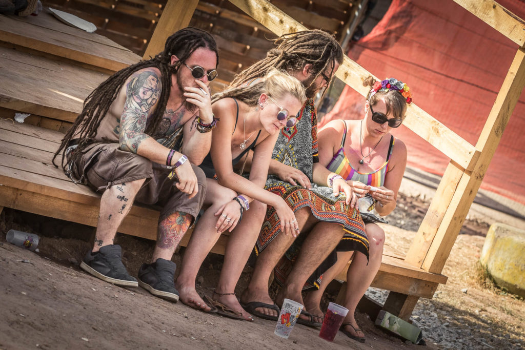A colour image of 4 festival goers sat having a smoke during a lull in proceedings at Nozstock in 2018. 3 of the 4, a lady and 2 men sport dreadlocks whilst the other lady has her hair in a ponytail. 2 of the four smoke hand rolled cigarettes whilst the remaining 2 can be seen rolling theirs.