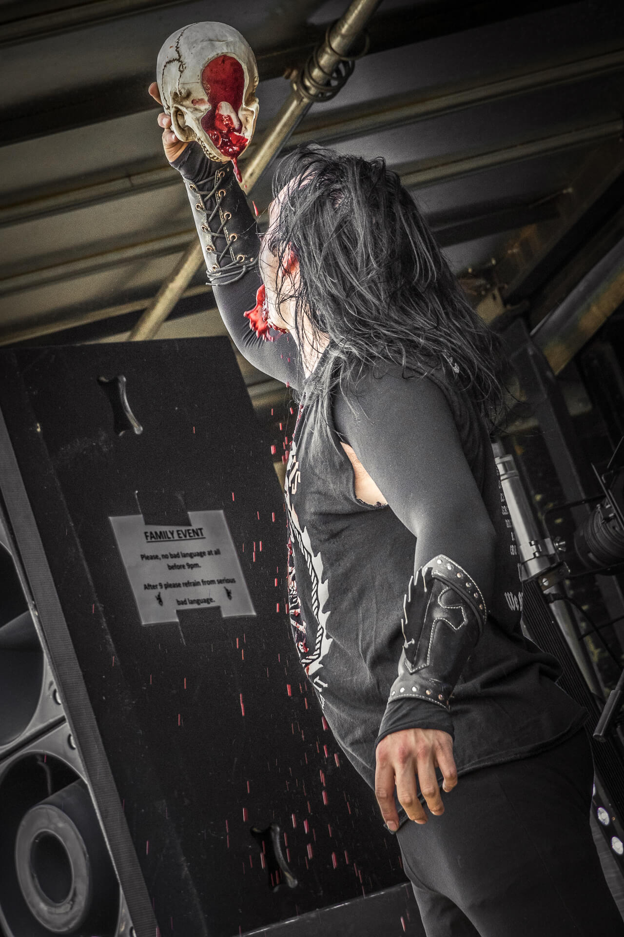 A colour image of Johnny Law as he holds aloft a human skull prop and drinks fake blood from it whilst on stage at The Drunken Monkey Rock Festival. Johnny is frontman of WASP tribute band Electric Circus.