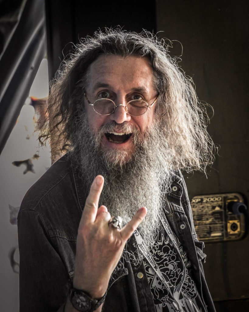 A 3/4, close in view, taken chest upwards colour image of 'Krusher' at the side of the stage at the Drunken Monkey Rock Festival. Krusher is seen smiling and making a 'Horns Up' gesture with his right hand. The man is a legend in Heavy Metal circles having been responsible for some classic album cover designs.