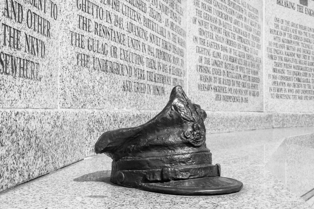A black & white close up image of a bronze Rogatywka, the hat worn by officers in the Polish Army. It is in front of one of the 4 surrounding plaques at the Polish Forces War Memorial at the National Memorial Arboretum.