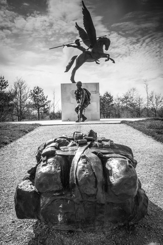 A thought evoking black & white image of the Parachute Regiment and Airborne Forces National Memorial at the National Memorial Arboretum at Arlewas; the image shows Bellerophon sat astride Pegasus, with his raised spear, and a Paratrooper pulling his Bergan towards the statue. The image is taken from close to the Bergan looking towards Bellerophon and the Paratrooper.