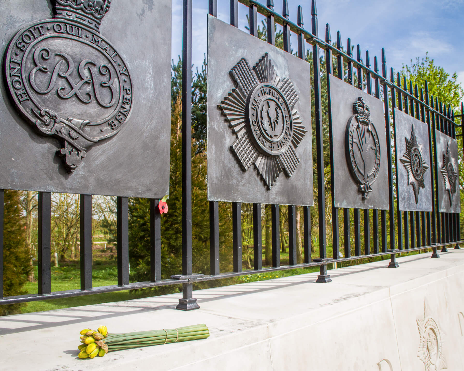 The decorative iron railings (which represent the railings at Wellington Barracks, London) seen here at the National Memorial Arboretum as part of the Household Division Memorial. In this colour image the 5 insignia of the Foot Regiments (as they line up on parade) can be seen; they are, The Grenadier Guards, The Scots Guards, The Welsh Guards, The Irish Guards, and The Coldstream Guards, underneath them is a small bunch of daffodils.