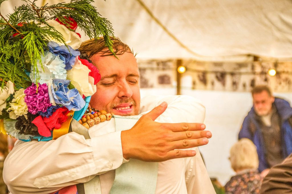 A head & shoulders image of 2 of the Earlsdon Morris Men at the Bromyard Folk Festival in 2018. Seen in a head & shoulders shot they are hugging and back slapping after performing. The one facing the camera has his eyes closed and wrinkles his nose as they embrace, the one that looks away still wears his multicoloured multifoilage festooned hat.