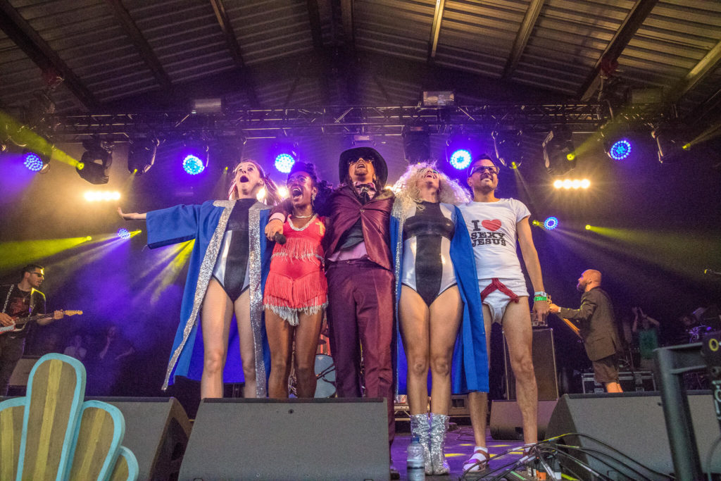 Members of the band 'Oh My God, It's The Church' take the audiences applause and adulation at the end of their set at the Nozstock Festival in 2018. Seen in the front centre of the stage 5 of the 7 members stand next to one another smiling and laughing.