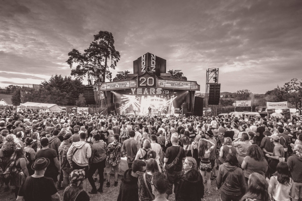 A relatively wide angle sepia toned image of the Nozstock main stage taken in 2018. Taken from the rear of, and from slightly above the crowd looking forward towards stage where performers are on stage.