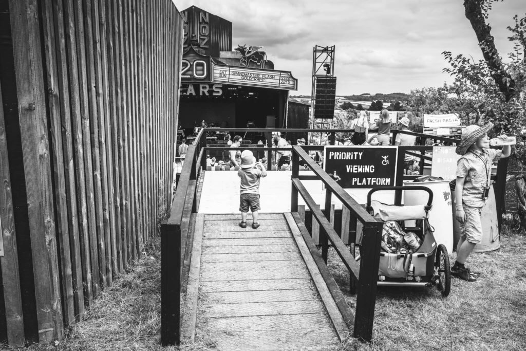 A very young festival goer, seen here in black and white and who seems to have escaped from his pushchair, stands alone on the disabled priority viewing platform overlooking the main arena area at Nozstock. Shorts, beanie style hat, and sandals seem to be the in form of dress!