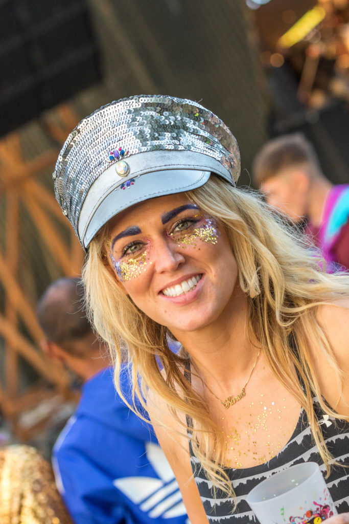 A chest up colour image of a female festival goer at Nozstock. As she smiles for the camera she wears a silver sequin peaked hat (over her long flowing blonde hair). She has gold glitter stars under her eyes and across her cheeks.