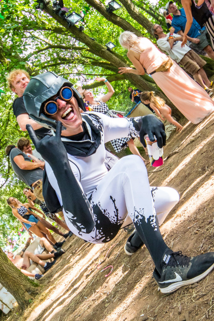 A Nozstock festival goer getting in the spirit of it all near the Elephant's Grave stage. He is seen in this colour image taken at an angle of about 45 degrees, grinning in a black and white jumpsuit, complete with gloves and helmet. He also wears a pair of blue tinted goggles, and carries a small black backpack.  The Elephants Grave is a haven for both dub and reggae in the day, and house and techno when night falls.