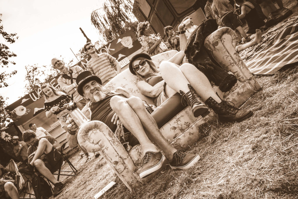 A sepia image of a couple of festival goers sat on a settee during a lull in proceedings at the Nozstock Festival. Taken at 45 degrees, the gent holds a pewter tankard whilst the lady holds a plastic glass, both have their left leg crossed over their right, and both display a wry smile for the camera.