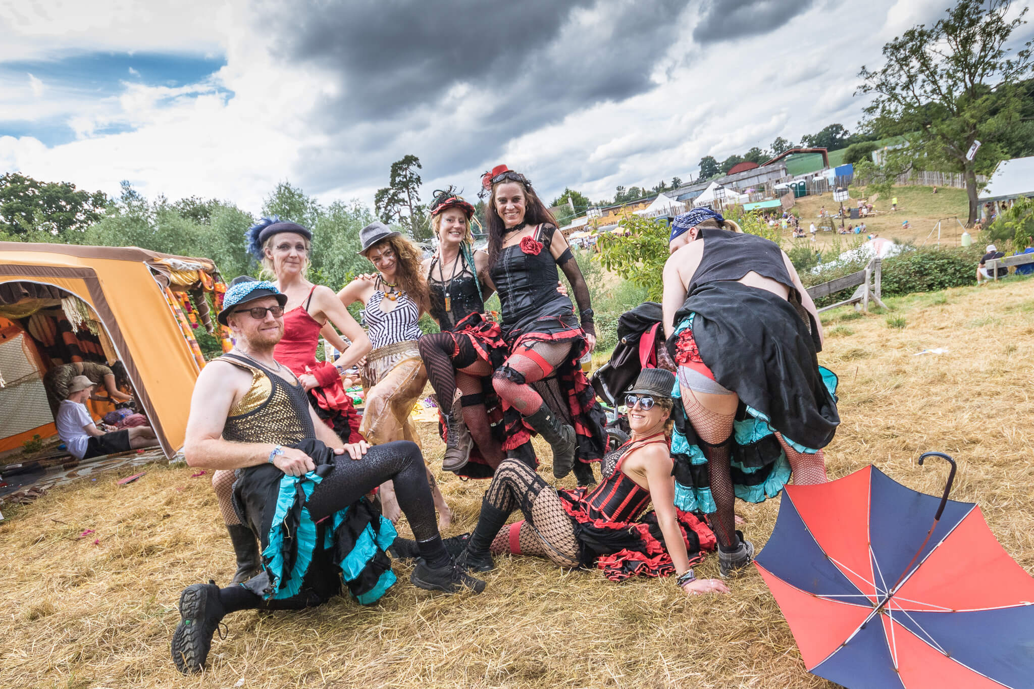 An informal group shot of a group of festival goer's (all in fancy dress) in the camping area of Nozstock. Some are stood, in a Can Can Dancer pose, one kneels, one sits, and one gentleman bends over to display his under garments , and the tops his fishnet stockings.