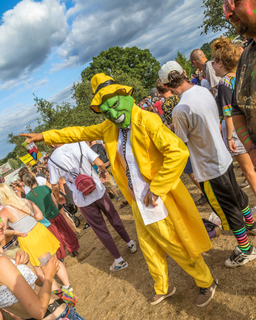 A reveller at Nozstock dressed as Stanley Ipkiss, the Superhero (played by Jim Carrey) in 1994 film The Mask. Stood in the crowd and seen pointing he wears the full yellow outfit along with a green mask.